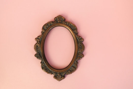 Vintage round picture frame on pastel pink wall.