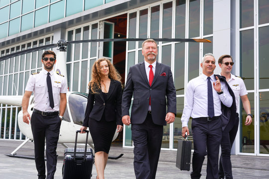 Group of Businessmen and Pilots Walk with Confidence in front of the Helicopter.