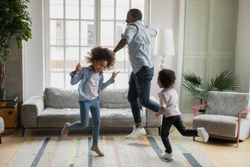 Active african funny dad little son and crazy daughter heavy metal or rock and roll lovers dancing in cozy living room relish life fooling around listening cool music scream with joy enjoy party hard Fotobehang