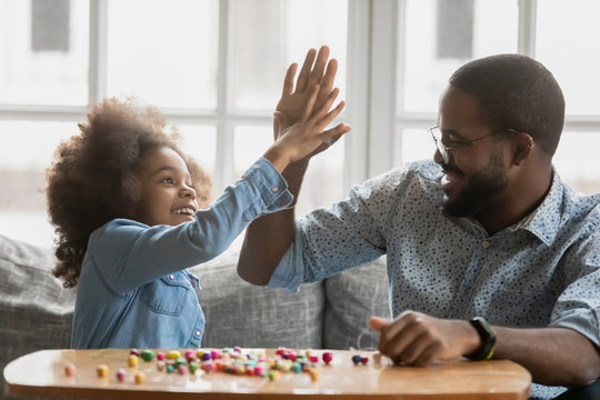 Seated on couch happy African little daughter raise hand gives high five to father, family spend time together using colorful wooden beads starts make handmade craft things, pastime and hobby concept