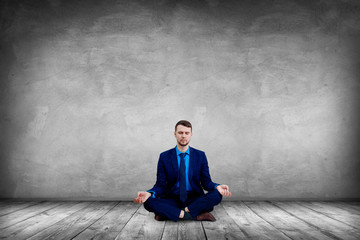 Calm businessman sitting in lotus pose and meditating. Wall mural
