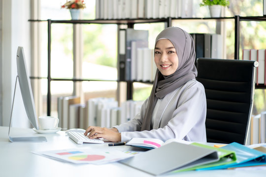 Muslim Business Woman in Hijab with Documents at Workplace in Office.