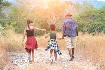 African American Family On Hiking Adventure Through Forest.