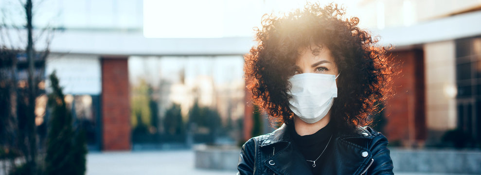 Protected caucasian woman with curly hair is posing in a sunny day while looking at camera and wearing a special white mask