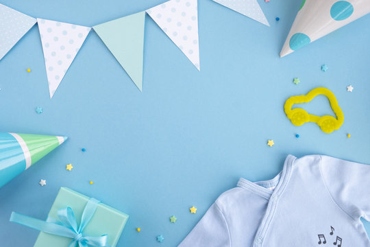 Newborn baby boy accessories and festive decoration. Birthday caps, gift box, confetti, toy car, party flags and blue clothes bodysuit. Top view, flat lay, copy space, frame
