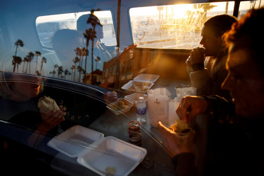 The Stubbs family eats a take-out dinner inside a Volkswagen Bus as authorities encourage social distancing to prevent the spread of coronavirus disease (COVID-19) in Newport Beach, California