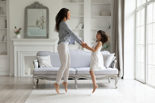 Happy young mom and cute little preschooler daughter have fun dancing jumping in living room together, overjoyed millennial mother or nanny feel playful entertain at home with small girl child
