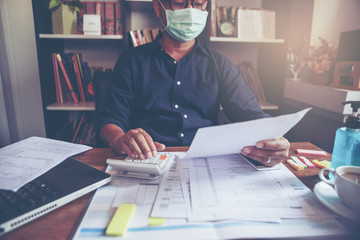 Budget planning concept, Accountant wear mask is calculating the company's annual tax. Calendar 2019 and personal income tax forms for those who have income under US law placed on home desk.