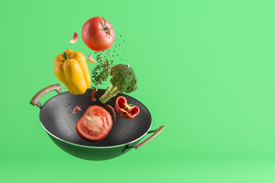 Fresh colored vegetables flying from the wok. Green studio background