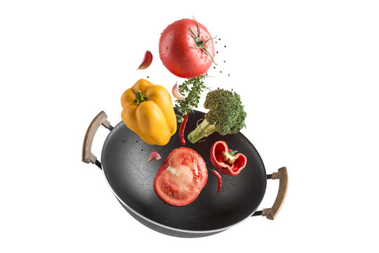 Fresh multicolored vegetables fly over a wok frying pan. White isolated background.