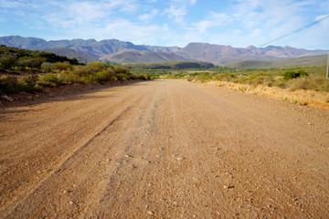 Fototapeta Long open dirt road in mountain landscape obraz