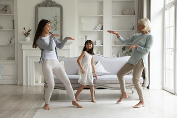 Overjoyed three generations of women have fun dancing in living room together, happy little...