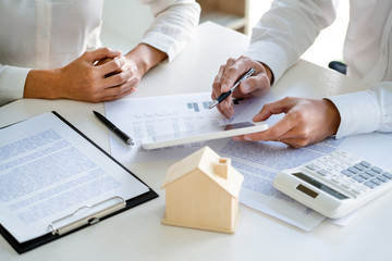 Real Estate Agent broker or House developer showing contract for buying house agreement to consultant employee.