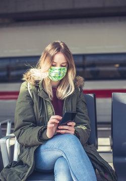 junge Frau mit Mundschutz und smartphone auf dem Bahnhof