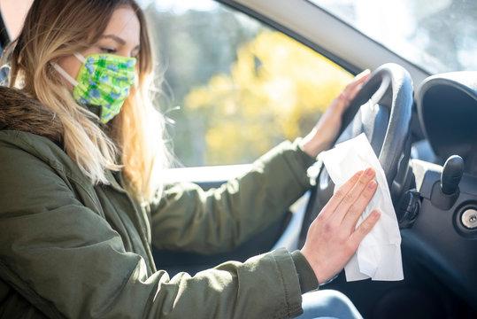 junge Frau desinfiziert Lenkrad im Auto
