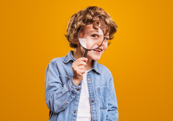 Cheerful boy with magnifying glass looking at camera