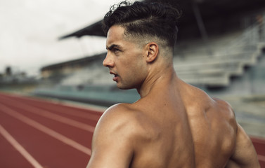 Healthy young man standing on track field Fotomurales