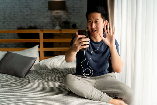 Portrait of happy 30s aged Asian man in casual clothing making facetime video calling with smartphone at home. He's waving at people on phone screen. Social distancing concept