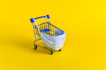 Blue shopping cart with medical mask for virus protection on yellow background. Creative concept of healthcare and safe shopping on coronavirus quarantine Wall mural