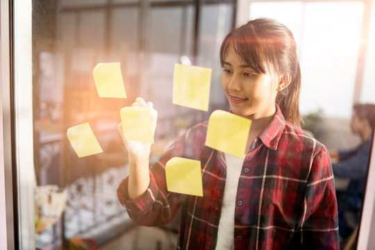 beautiful asian office worker woman using a marker pen writing ideas information or data on yellow sticky notes, working for business, company, or self-business owner, smiling wearing casual clothing