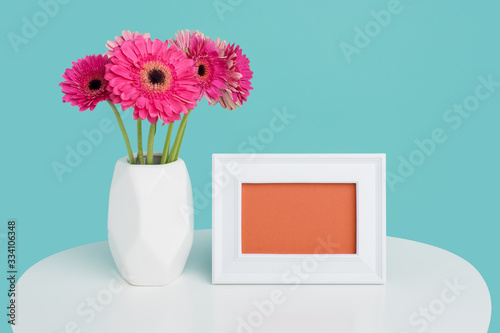 Happy Mother's Day, Women's Day, Valentine's Day or Birthday Background. Beautiful dark pink gerbera daisies in a vase and an empty picture frame greeting card.