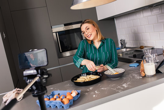 Young woman recording vlog at home in kitchen making croissants.