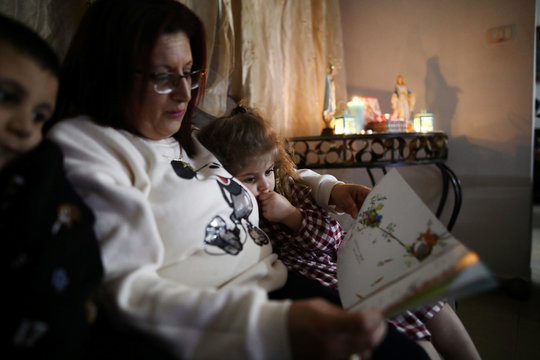 Palestinian woman Jizelle Sara, 42, reads a book to her children Elie, 6, and Silva, 5, while observing a partial lockdown to curb the spread of the coronavirus disease (COVID-19) at their home in Jerusalem