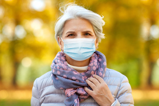 health, safety and pandemic concept - sad senior woman wearing protective medical mask for protection from virus sitting on bench at autumn park