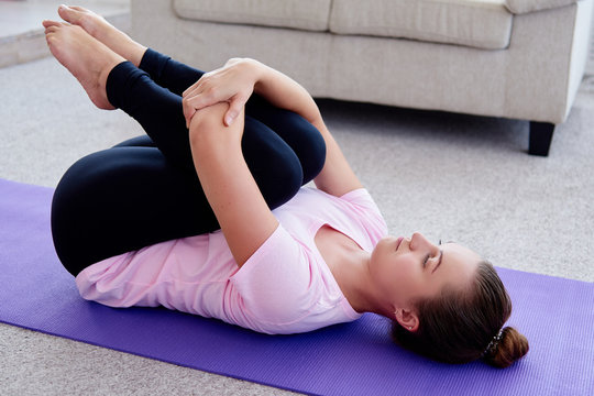 Portrait of young woman practicing apanasana pose on mat at home indoor, copy space. Apanasana. Knees to chest pose. Practicing yoga. Wellness and healthy lifestyle