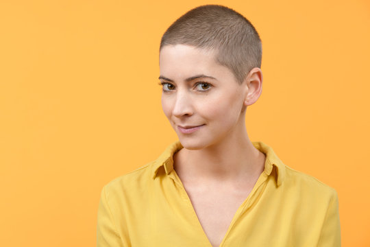 Studio portrait of a beautiful young caucasian woman with shaved head against bright yellow background. Cancer survivor portrait.