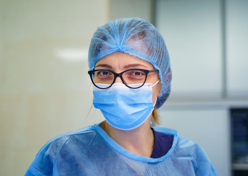 Doctor or nurse smiling behind surgeon mask. Closeup portrait of young woman model in blue medical scrub. Coronovirus epidemic. Ambulance station. Intensive care unit with Pneumonia diagnosting.
