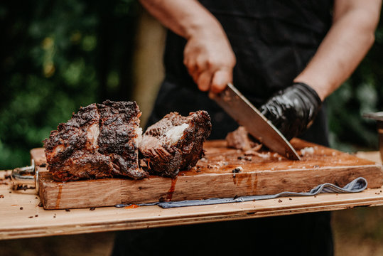 man is cutting meat on wooden table
