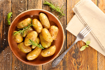 Wall Mural - roasted potato and rosemary on wood background