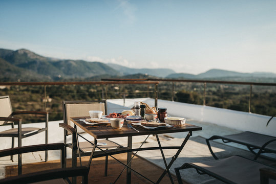table and chairs with breakfast on terrace in front of mountains