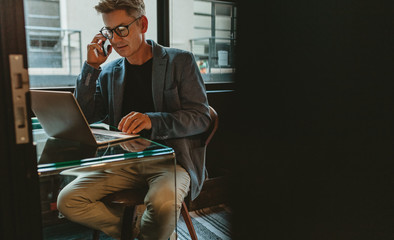 Entrepreneur discussing work over mobile phone at his desk