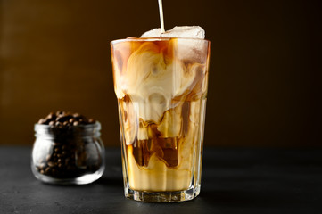 Milk is poured into a transparent glass with iced coffee on a black table, brown background. Frozen cream swirls in a glass. Copy space, horizontal orientation.