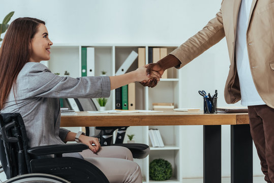 Disabled employee and african american recruiter shaking hands at job interview in office