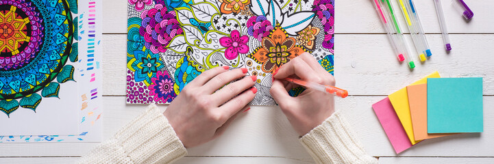 Adult coloring book, stress relieving trend. Art therapy, mental health, creativity and mindfulness concept. Flat lay close up on woman hands coloring an adult coloring book web banner. Fototapete