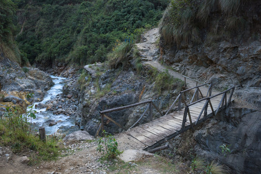Small wooden bridge crossing a river along the Salkantay Trail, Peru