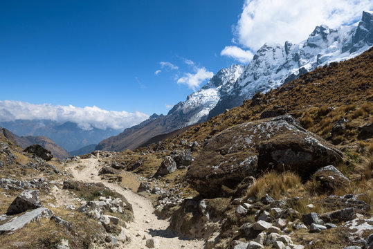 Rocky paths and green valleys surrounded by snowcapped mountains on the Salkantay Trek, Peru