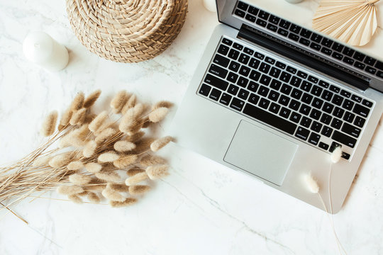 Laptop, tan plant branches bouquet on marble table. Home office desk workspace. Flat lay, top view business, work concept.