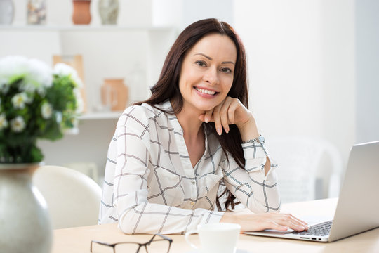 Portrait of business woman looking at camera at workplace in a home office