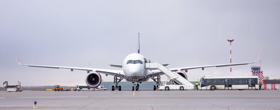 Airport land crew doing flight service for passenger airplane, before the flight departure. Wide panorama view.