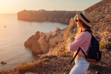 Traveler hiking by White beach on Aegean sea Santorini island, Greece enjoying landscape. Woman backpacker on vacation Fotobehang