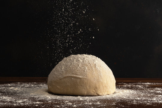 Pastry chef sprinkles flour on fresh raw dough for bread or pizza on a dark background.