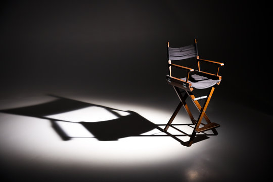Directors chair stands in the beam of light. Space for text. Vacant chair. The concept of selection and casting. Shadow and light.