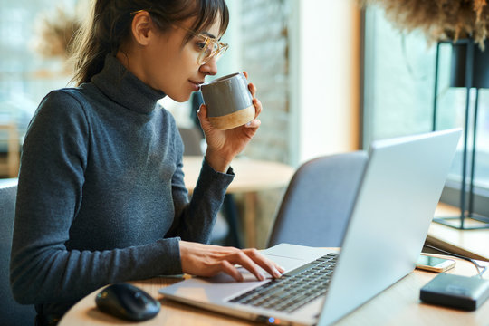 Young beautiful woman in eyeglasses enjoying coffee during work on portable, laptop, computer. Female copywriter sitting at desk and typing on keyboard, working on project, writing down ideas into