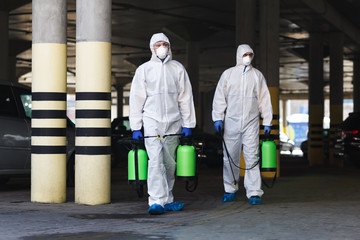 Men in coronavirus suits holding disinfection chemicals outdoor