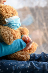 A girl in a blue sweater sits on a windowsill and holds a teddy bear in a medical protective mask. Self-isolation and quarantine during a pandemic. Stop coronavirus concept. Crop view, copy space.