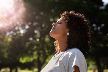 Young woman standing outdoors feeling the sun on her face